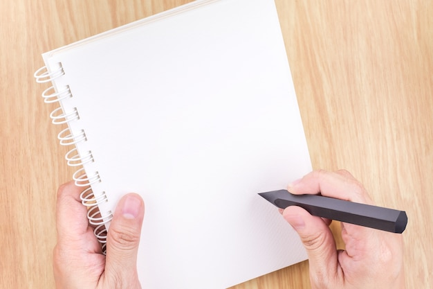 Hand holding black pencil and empty white open book above wood desk