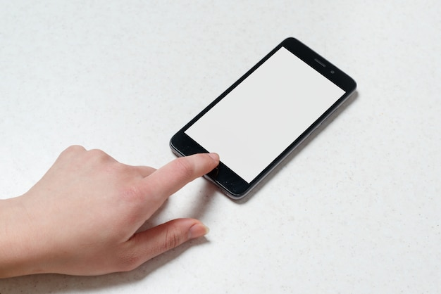 Hand holding the black phone with blank screen and modern frame less design