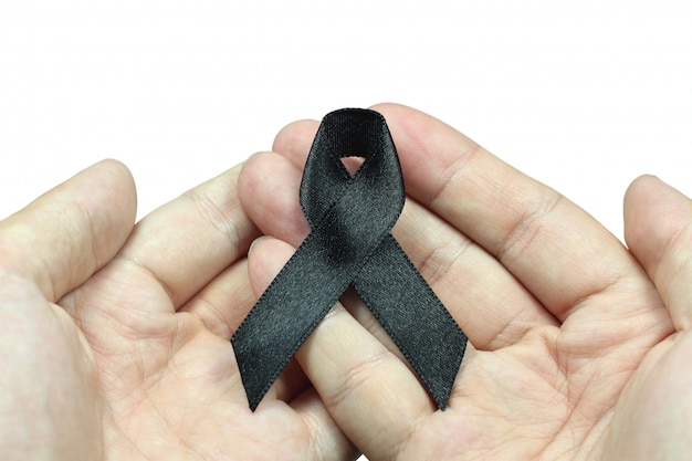 Hand holding black ribbon for mourning concept on white