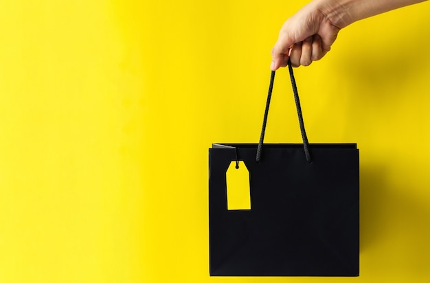 ブラックフライデーのショッピングセールのコンセプトのための黄色の背景を持つ空白の黄色の値札が付いている黒い買い物袋を持っている手。