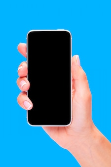 Hand holding black smartphone with blank screen on blue background