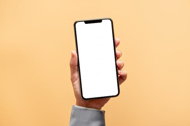 손을 노란색 배경에 흰색 스크린 검은 스마트 폰 들고.