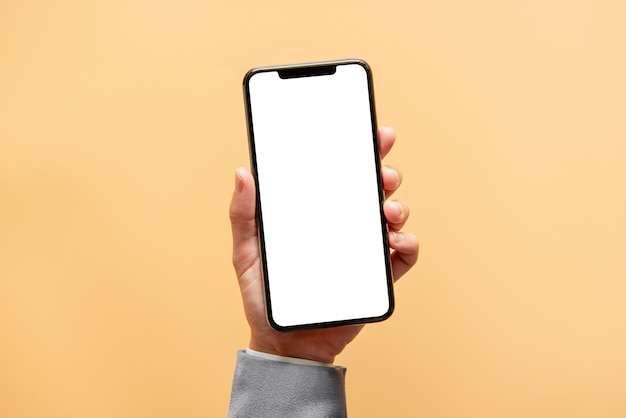 Hand holding black smartphone with white screen on yellow background.