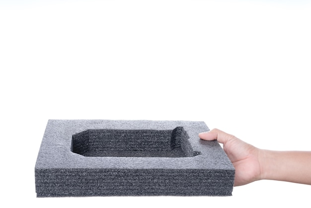 Hand holding black sponge foam in a shape of electronic or computer part