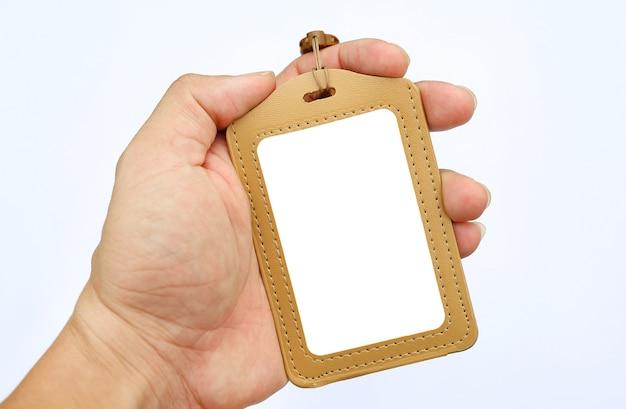 손을 잡고 흰색 배경에 빈 배지 카드와 끈