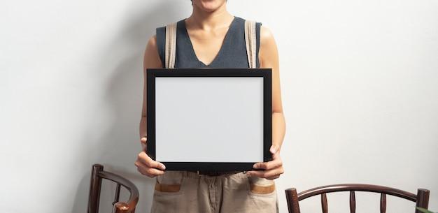 Hand holding blank black photo frame for design