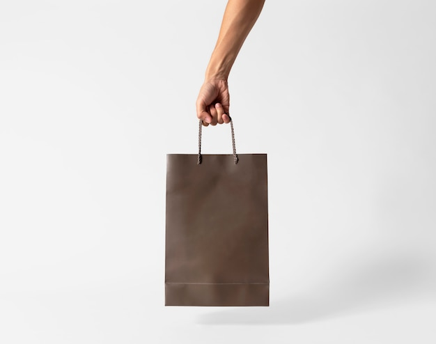 Hand holding blank brown paper bag for mockup template advertising and branding on gray background.