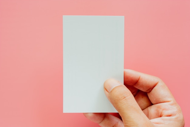 Hand holding blank business cards on pink background