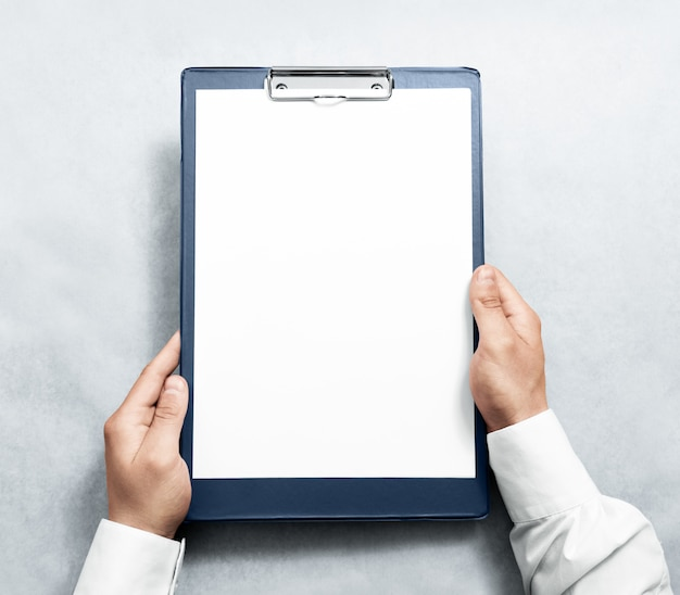 Hand holding blank clipboard with white a4 paper design