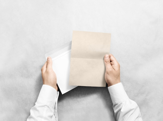 Рука держа пустой конверт и макет письма крафт, изолированные