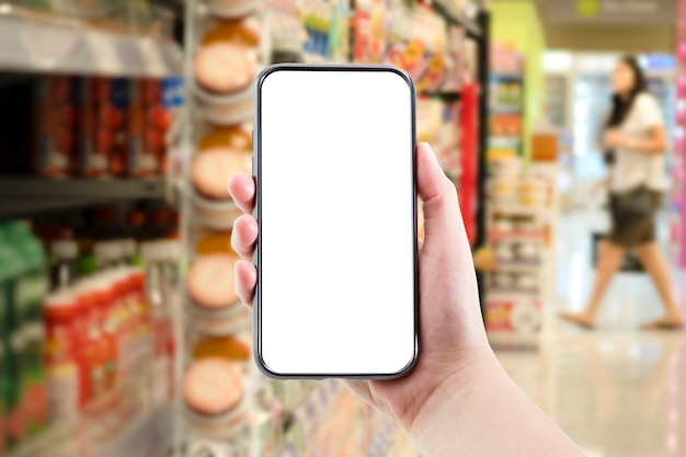 Hand holding blank form of mobile phone with supermarket or shopping mall background. online shopping or e commerce concept.