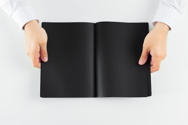 Hand holding blank opened book mock up