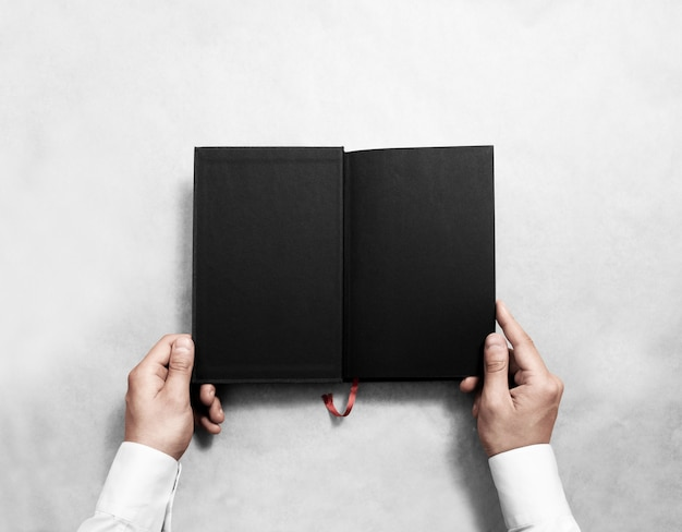 Hand holding blank opened book with black half title