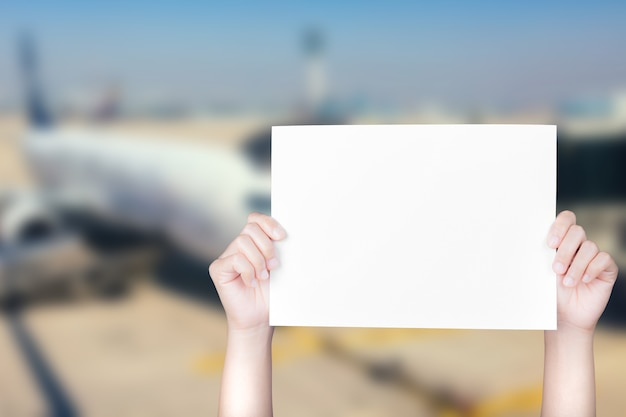 비행기 배경이 흐릿한 빈 종이를 들고 있는 손