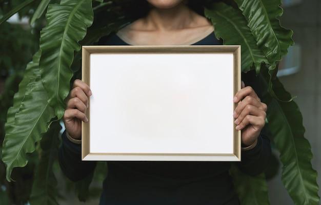 Hand holding blank photo frame