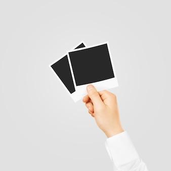 Hand holding blank photo frames