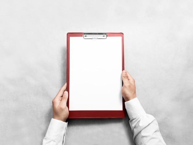Hand holding blank red clipboard with white paper design