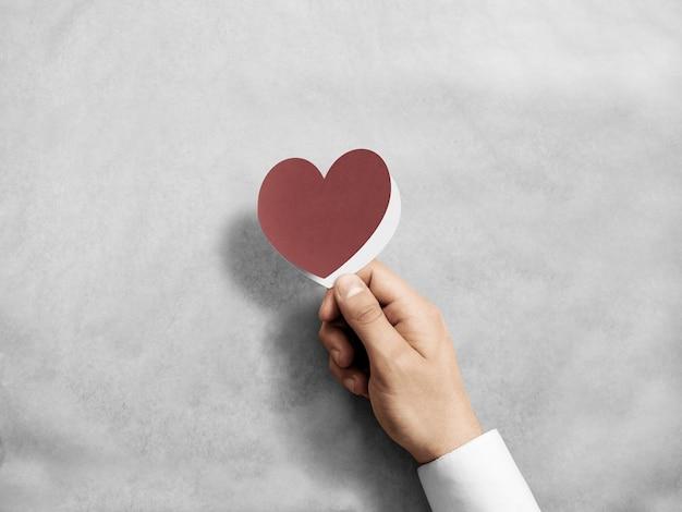 Рука держит пустой красный макет карты валентина