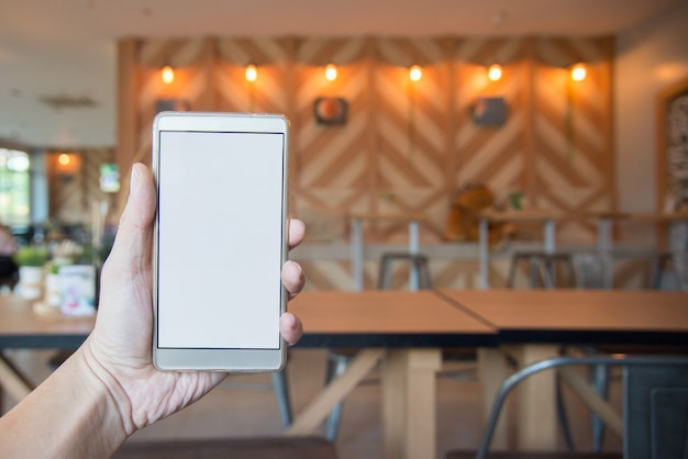 Hand holding blank screen of smart phone with blurred sitting on cafe background
