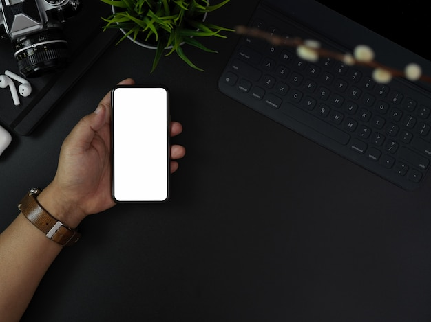 Hand holding blank screen smartphone above dark modern office desk with office supplies and decorations