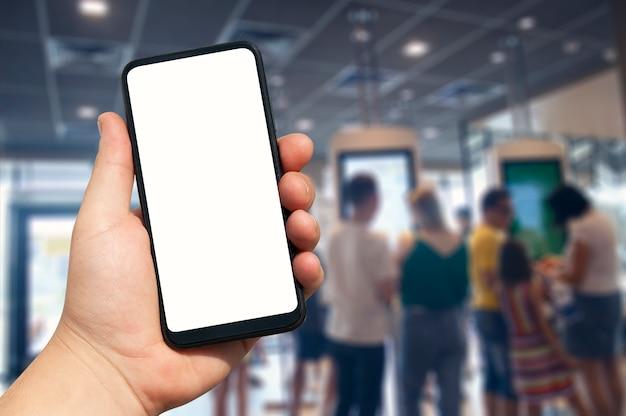 ぼやけている人々に対して空白のスマートフォンを持っている手