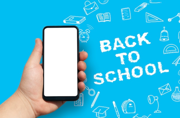 Hand holding blank smartphone on back to school background