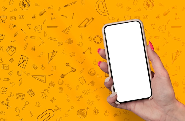 Hand holding blank smartphone on stationery school doodles background