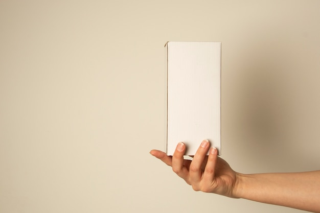 Hand holding blank white box , mock up. copy space. packing and delivery concept.