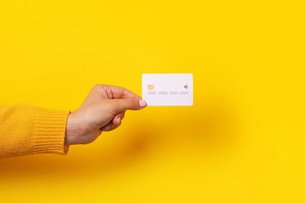 空白の白いクレジットカードのモックアップ、黄色の背景の上に電子チップとカードを持っている手