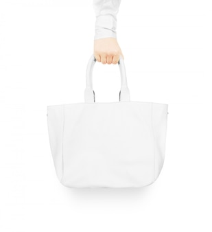 Hand holding blank white women's leather bag mock up isolated.