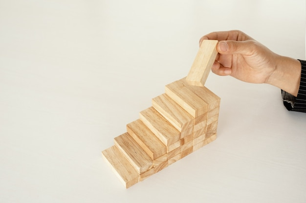 Hand holding block wood game concept risk of management and strategy plan growth business teamwork