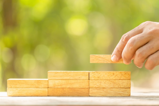 Hand holding blocks wood to make step grow up on green blur with copy space for text or design concept for business concept