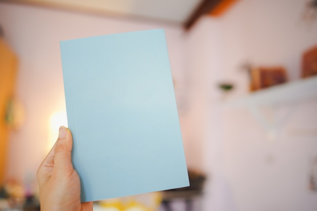 Hand holding a blue book with a blank cover for putting text in the room.