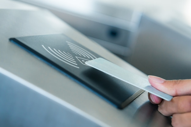 Hand holding blue card to access electronic entrance scanner