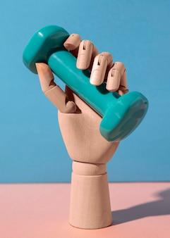 青いダンベルの静物を持っている手