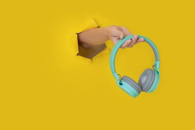 破れた黄色い紙に青いヘッドフォンを持っている手。紙の穴にヘッドホンを持って手。音楽のコンセプト。テキスト用のスペースのあるクリエイティブな写真。トレンディなミニマルスタイル