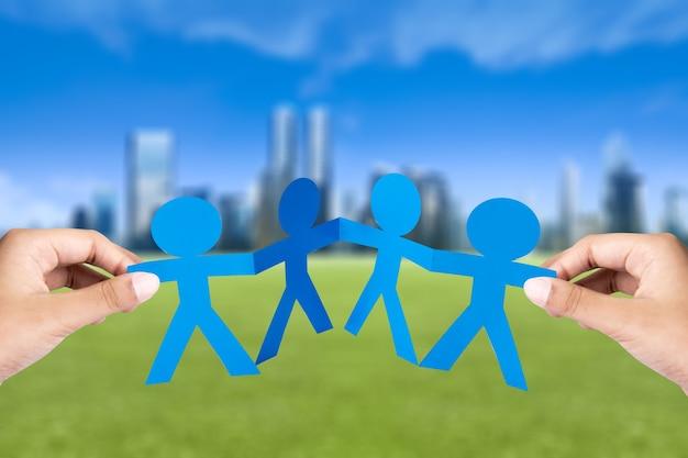 Рука синих людей бумаги, взявшись за руки с фоном городских пейзажей. концепция всемирного дня народонаселения