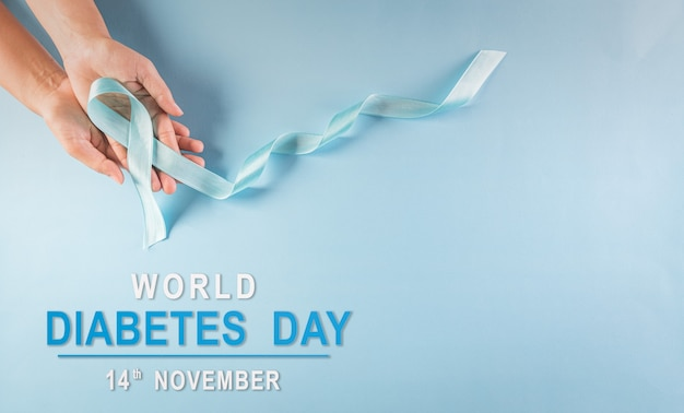 Hand holding blue ribbon symbolic bow color raising awareness in diabetes day