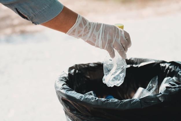 Hand holding bottle garbage putting black bag at park