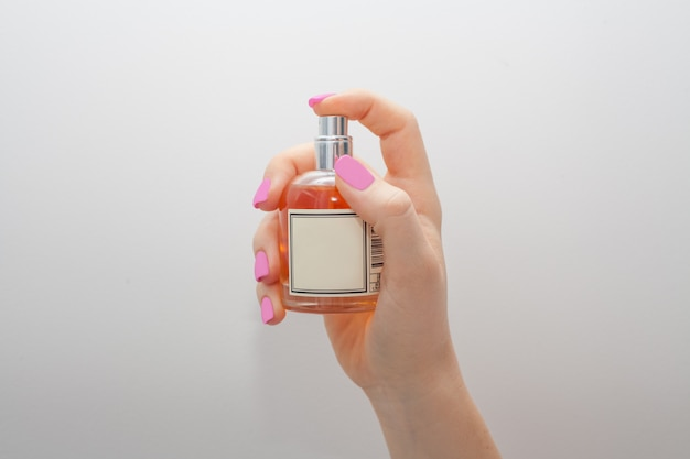 The hand holding the bottle holds the index finger on the sprayer, on a white wall. the concept of perfume or women's care.