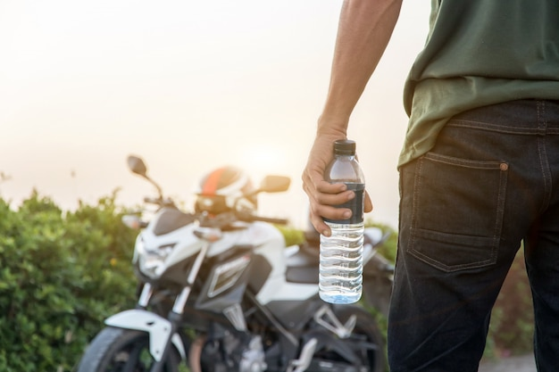 Рука держит бутылку воды с большим велосипедом фоном, летние каникулы на открытом воздухе и вид в вечернее время