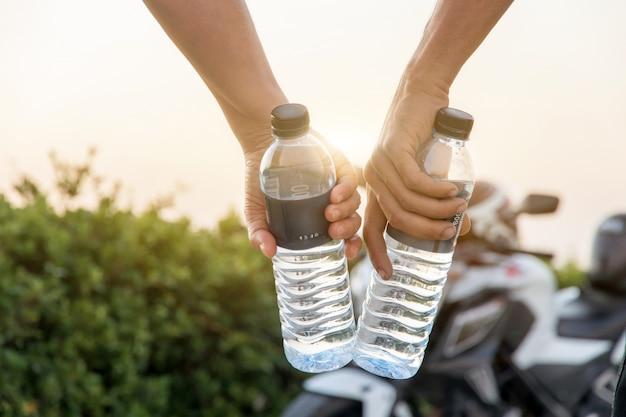 大きな自転車、屋外の夏の休日休暇と夜のビューでボトルの水を持っている手