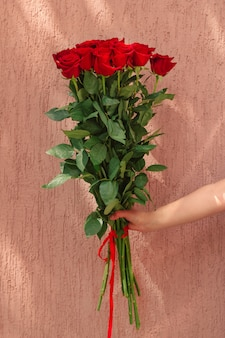 Hand holding bouquet of red roses against rough wall