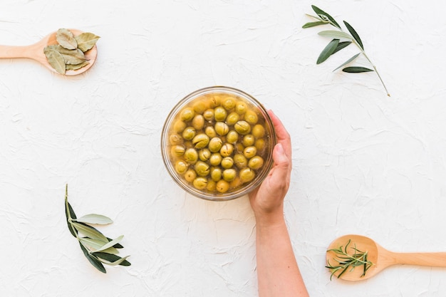 Hand holding bowl of olives with herbs on wooden backdrop
