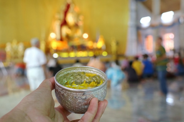Hand holding bowl of scented water to sprinkle water onto a buddha. songkran festival.