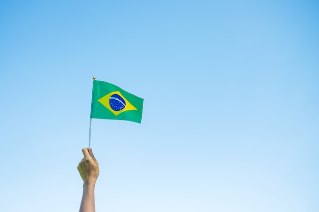 Hand holding brazil flag on blue sky background. september independence day and happy celebration concepts