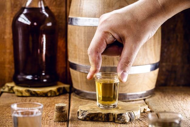 Hand holding brazilian distilled beverage, on rustic still background.