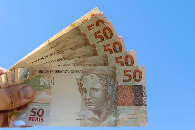 青い空を背景にブラジルの紙幣を持っている手