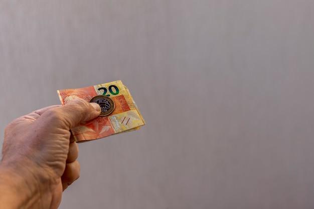 テキスト用のスペースのあるブラジルのマネーコインと紙幣を持っている手。