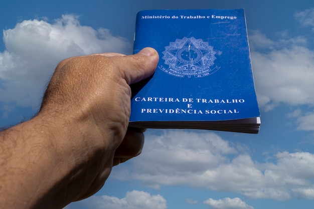雲と空にブラジルのワークブックを持っている手。